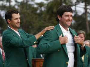 Masters champion Watson is helped with his traditional green jacket by last year's champion Scott of Australia after the final round of the Masters golf tournament at the Augusta National Golf Club in Augusta